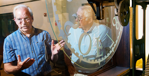 Bruce Hannon, a UI geography professor, shares the story of the Urbana campus's 1878 tower clock, now housed in the mechanical engineering laboratory, during a recent tour of historic campus clocks. Hannon, who restores clocks as a hobby, will offer tours of the campus clocks this fall.