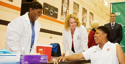 Illinois women's basketball coach Jolette Law (seated) prepares to receive the seasonal flu vaccine.