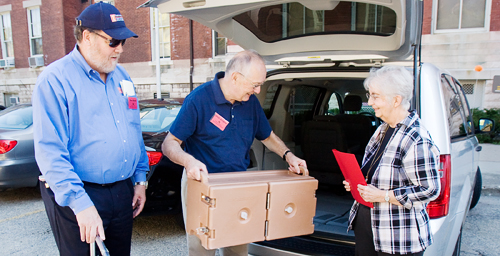 """Special delivery Volunteers load a meals into a vehicle parked outside the Illini Union in preparation for delivery to the homes of Meals on Wheels clients. The """"celebrity"""" volunteers delivered meals on Sept. 18 as part of an event honoring Dining Services' 45 years of participation with the Meals on Wheels program.  Click photo to enlarge"""