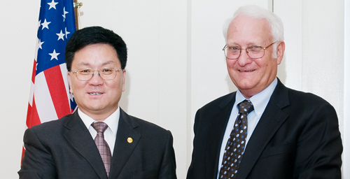 Global connections Robert Easter, right, dean of the College of Agricultural, Consumer and Environmental Sciences and interim provost, and Wenyu Han, president of Jilin University-Heping Campus, shake hands after signing an agreement that will facilitate research and teaching collaborations between the UI and Jilin in areas such as crop sciences, human nutrition and biotechnology.  Click photo to enlarge