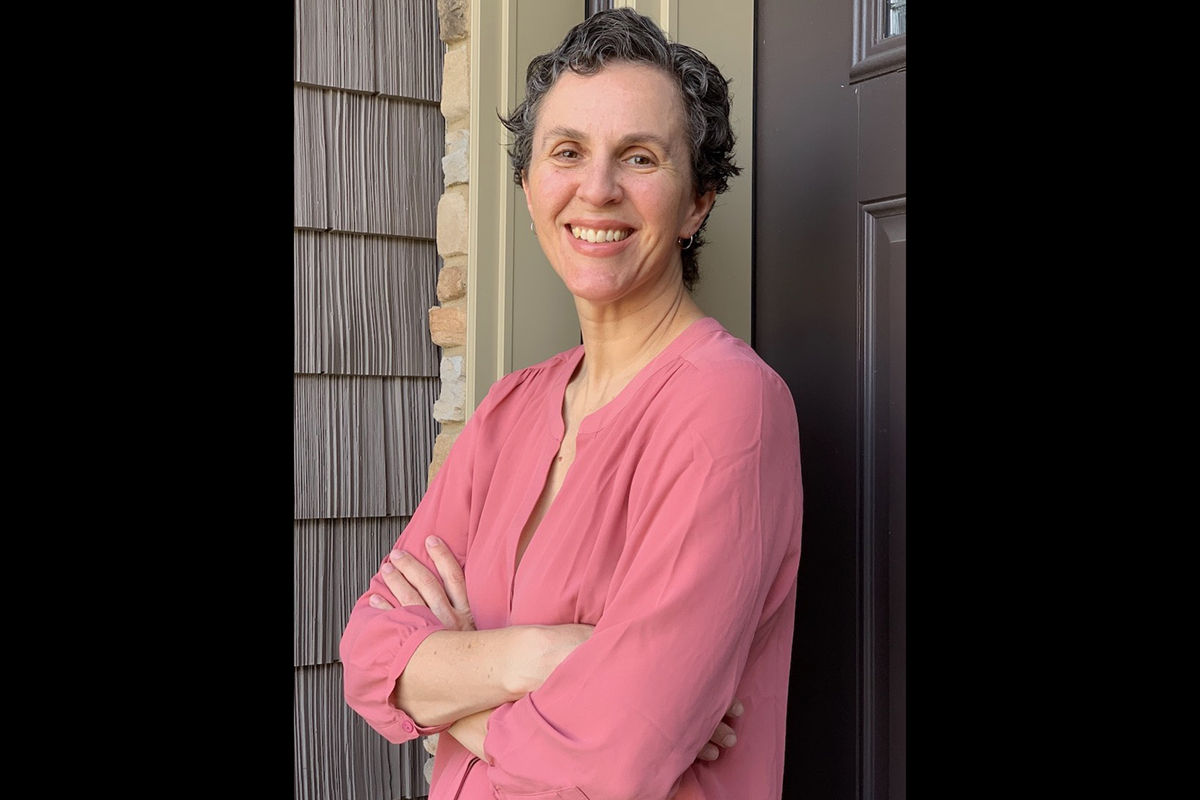 Sociology professor Ilana Redstone with her arms folded, leaning against a wall outdoors