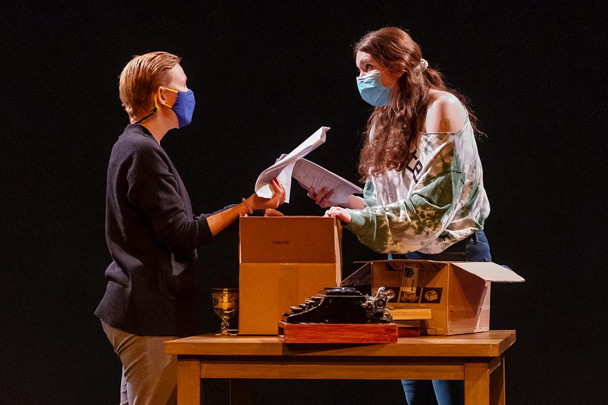 A theatre professor and a student actor perform on stage with a table with a box and typewriter between them.