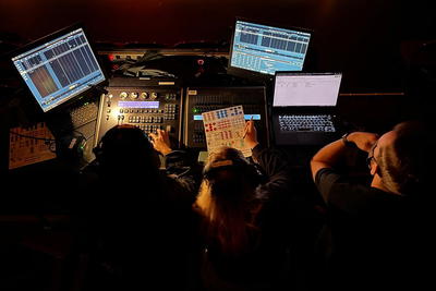 Lighting technicians seen from overhead sitting at the lighting board.