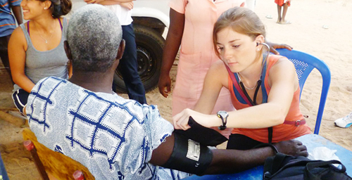Cristi Wales, a senior in kinesiology from Glen Elllyn, Ill., take blood pressure in the village of Ghada, Ghanam during the Frontiers International Health Society trip over winter break.