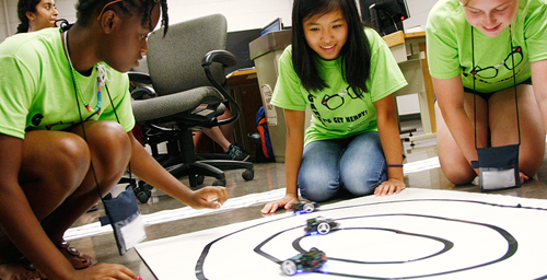 Campers in the robotics camp test small electric cars that they built and programmed. The cars are optically guided, so they are programmed to follow the black lines of tape.
