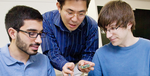 "Industrial design professor Cliff Shin, center, assists graduate student Ehsan Noursalehi, left, of Naperville, Ill., and engineering student Kevin Verre, of Niles, Ill., during a meeting of the ""A New Life for Laptops"" research group."