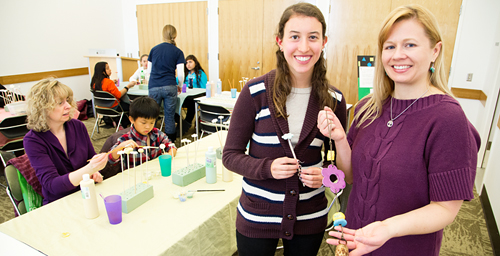 Pamela Hochwert, a senior in special education, standing left, and Michelle Bonati, a doctoral student in special education, at a Bens Bells event at Champaign Public Library.