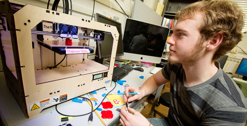 Sophomore Jason Hempstead uses a 3-D printer in the Illinois Geometry Lab to make solid shapes from plastic.