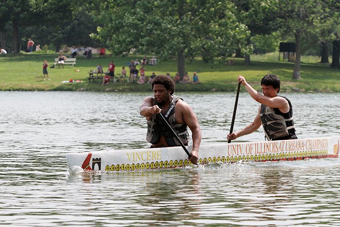 Boneyard Yacht Club members and U. of I. students Robert Butler, left, and Min Yin power their vessel, christened Vincere, during the races at Homer Lake on June 22.