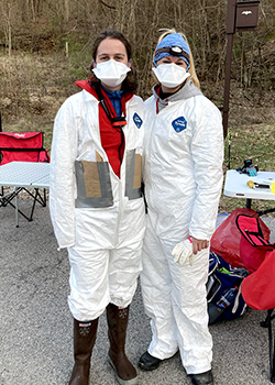 Researchers wear white jumpsuits, masks, rubber boots and gloves.