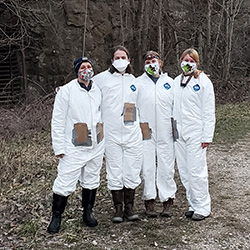 Four researchers in their protective attire stand together near their work site.