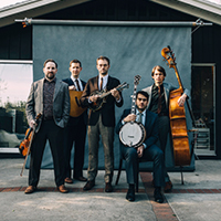 Photo of the five members of The Punch Brothers holding their string instruments in front of a canvas backdrop set up in the driveway of a home.