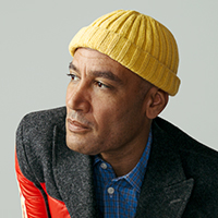 Photo of Ben Harper wearing a yellow knit cap and colorful jacket.