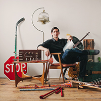 Photo of Joe Rauen with some of the musical instruments he's created from everyday objects.