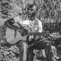 Black-and-white photo of Cedric Burnside sitting outside on a tree stump and playing his guitar.