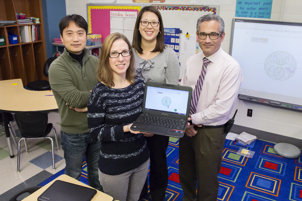 Researchers at Illinois and Champaign Unit 4 Schools are collaborating on a study that is exploring ways to embed computer science instruction within mathematics curricula. U. of I. special education professor Maya Israel (holding computer) is a co-principal investigator on the grant, funded by the National Science Foundation STEM C initiative. Shown with Israel are (from left) enrichment teacher Jinsoo Park, teacher Wendy Maa and principal Trevor Nadrozny, all of Kenwood Elementary School.