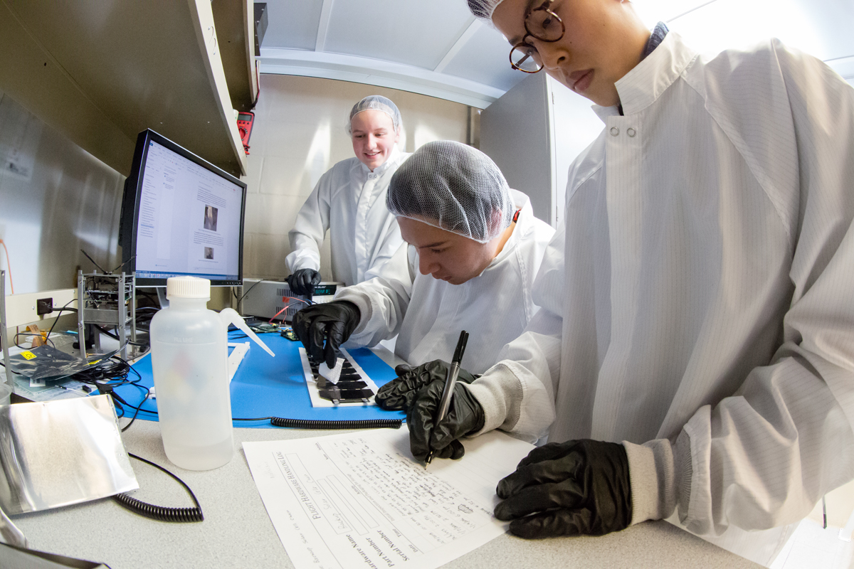 Students Dawn Haken, Jos Tuason and Osamu Miyawaki work on assembling and testing solar panels that will provide power for a CubeSat mission slated to launch in the fall.
