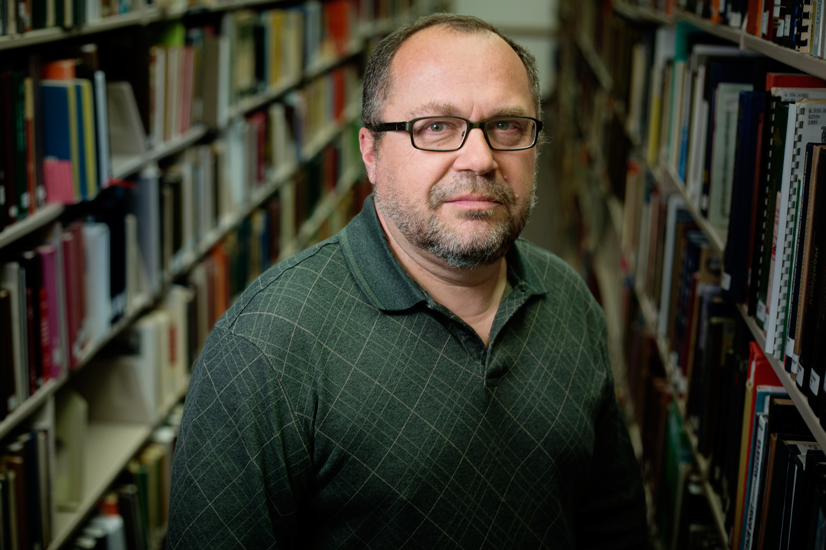 Jan Adamczyk, a senior library specialist, in between rows of books.