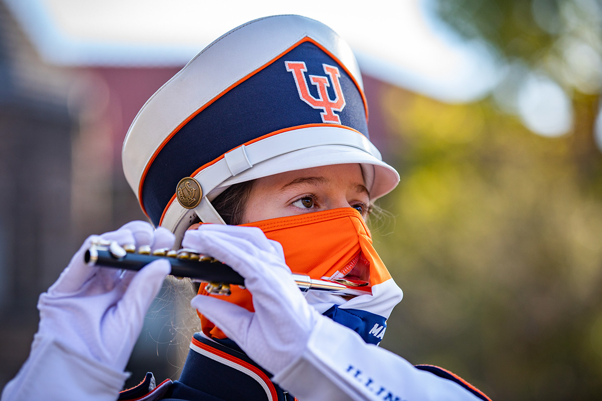 A Marching Illini piccolo player performs while wearing an orange and blue mask with a slit for the mouthpiece of her piccolo.