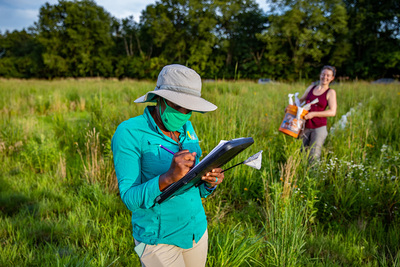 Entomology professor Alexandra Harmon-Threatt stands in a prairie with a clipboard in her hands. She is wearing a hat, a long-sleeved shirt and a mask. In the background, undergraduate student Sabine Miller carries a bucket of sandbags used to weigh down the tent traps.