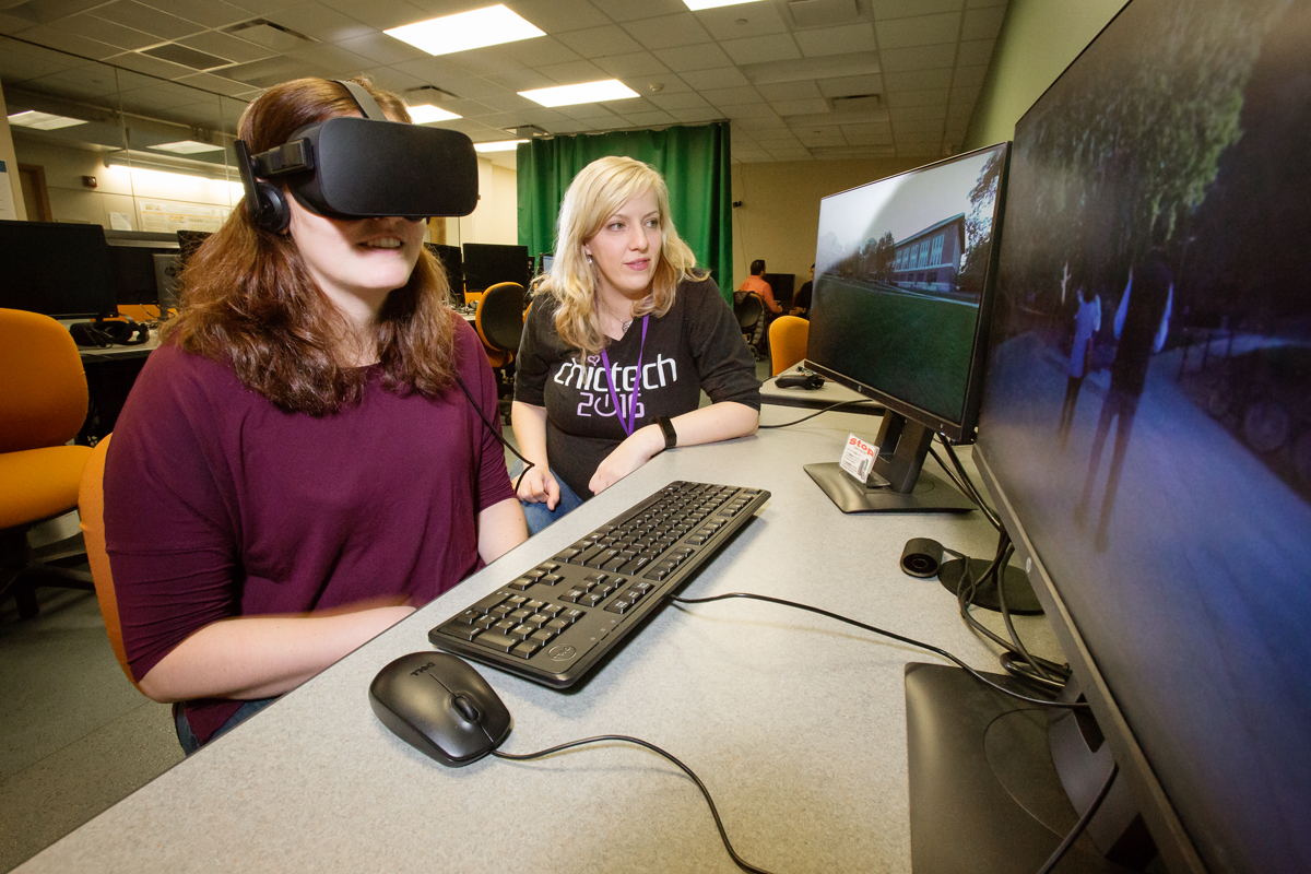 Photo of U. of I. computer science lecturer Anna Yershova and a student peering through a virtual reality headset.
