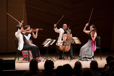 Image of Jupiter String Quartet performing on stage with their bows in the air.