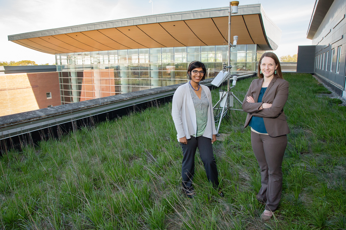 Graduate student Reshmina William, left, and civil and environmental engineering professor Ashlynn Stillwell pause on the green roof over the Business Instructional Facility at the University of Illinois. Their research is helping to simultaneously evaluate the performance of green roofs and communicate their findings with urban planners, policymakers and the general public.