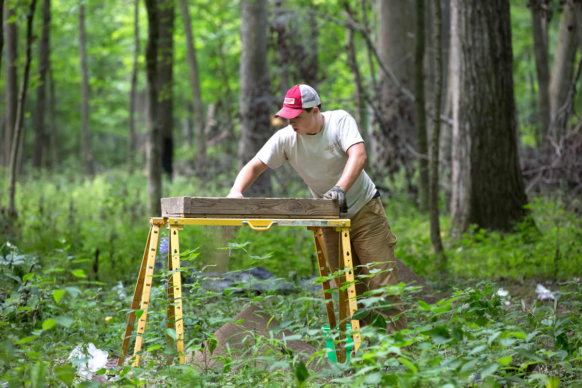 Researchers, including Parkland College student Kaleb Cotter, sift through materials uncovered in excavations of native mounds in Robert Allerton Park.