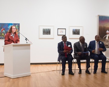 Krannert Art Museum Director Kathleen Harleman stands at a podium as, Kenyan Ambassador Robinson Njeru Githae, U. of I. Chancellor Robert Jones, Director General of the National Museums of Kenya Mzalendo Kibunjia sit next to each other in chairs at Krannert Art Museum, University of Illinois at Urbana-Champaign.