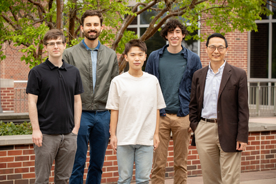 Photo of research team standing together outside in front of a brick wall and building.