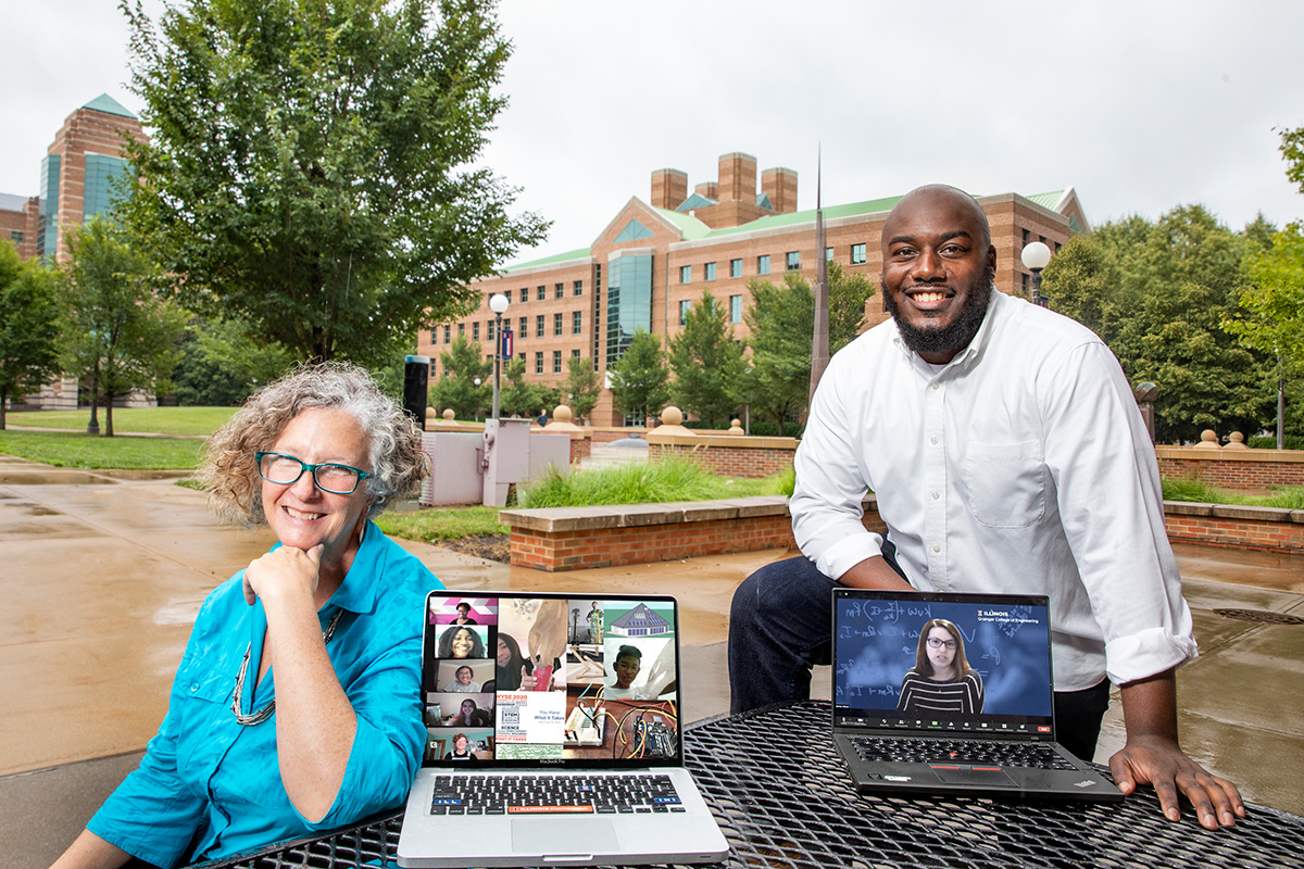 Bioengineering professor Jennifer Amos, seated, and postdoctoral research associate Gabriel Burks standing to her left with a laptop that displays public engagement coordinator Lara Hebert on the screen.