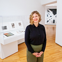 Photo of Amy Powell in a Krannert Art Museum gallery, with the abstract painting