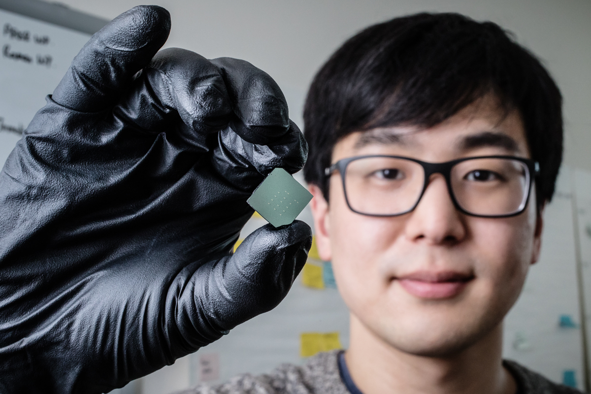 Illinois mechanical science and engineering student and lead author of a new study Benjamin Sohn holds a device that uses sound waves to produce optical diodes tiny enough to fit onto a computer chip.