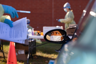 Man wearing face mask shown in car's side view mirror. In front of his car, workers wearing safety gear are preparing to test patients for COVID-19.