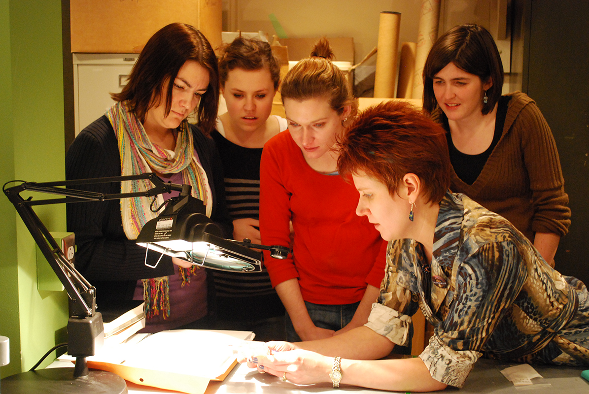 A Spurlock Museum staff member holds a object from the museum's collection under a lighted magnifier as students examine the object