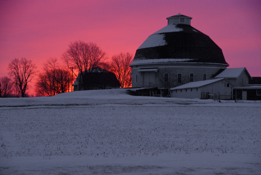 Red and purple sky behind a barn with snow-covered fields in the foreground.
