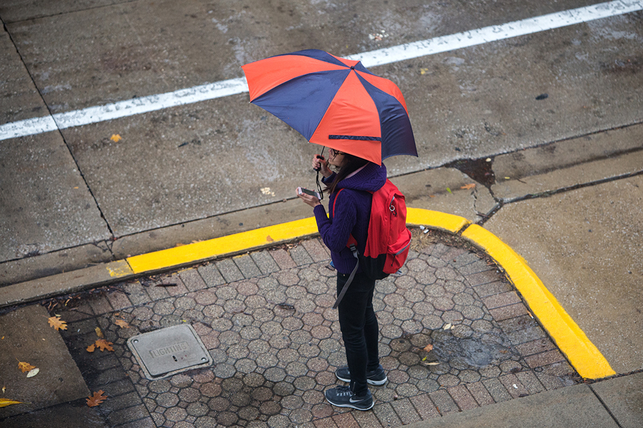 Student with an umbrella and a cellphone