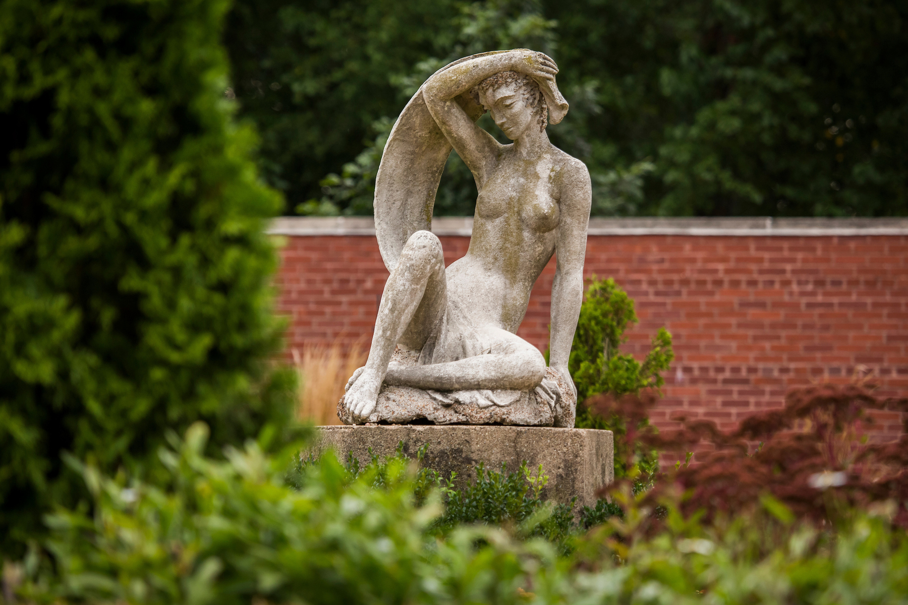 A stone sculpture of a girl holding a scarf