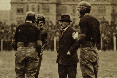 University of Chicago football coach Amos A. Stagg talks with three of his players during a game in 1916.