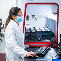 A technician works in a lab processing COVID-19 tests.