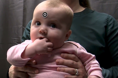 Photo of an infant in the IKIDS program seated on her mother's lap. The infant has a sticker on her forehead that allows an eye-tracking instrument to orient to her eyes.