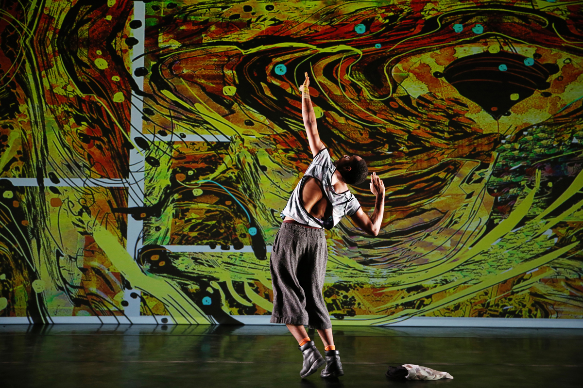 A dancer performs in front a swirling projection of colors