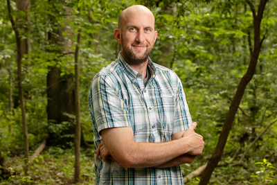 Portrait of researcher standing in the woods with his arms crossed.