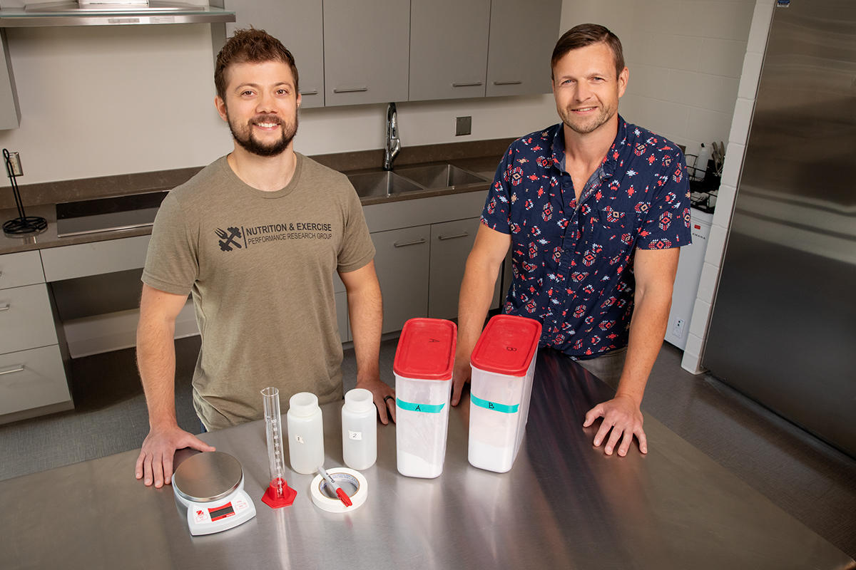 Photo of researchers standing in a laboratory with equipment and supplements used in the study on the bench in front of them.