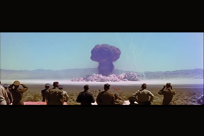 Observers look on during a Nevada nuclear test, one of many filmed by a secret Hollywood studio, its story chronicled by two Illinois professors.
