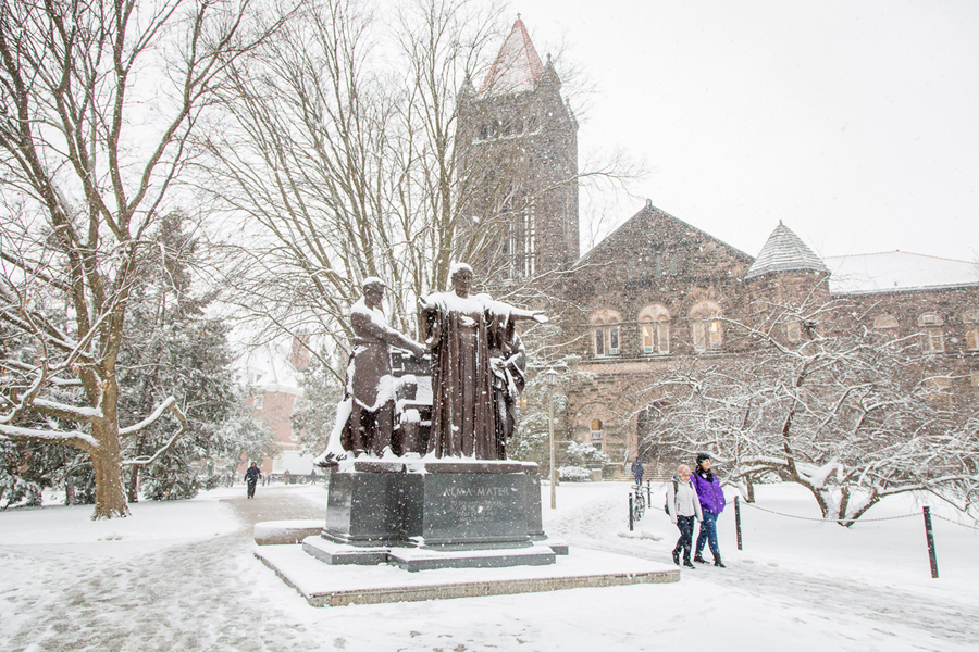Two people walk in the snow past the Alma Mater sculpture.