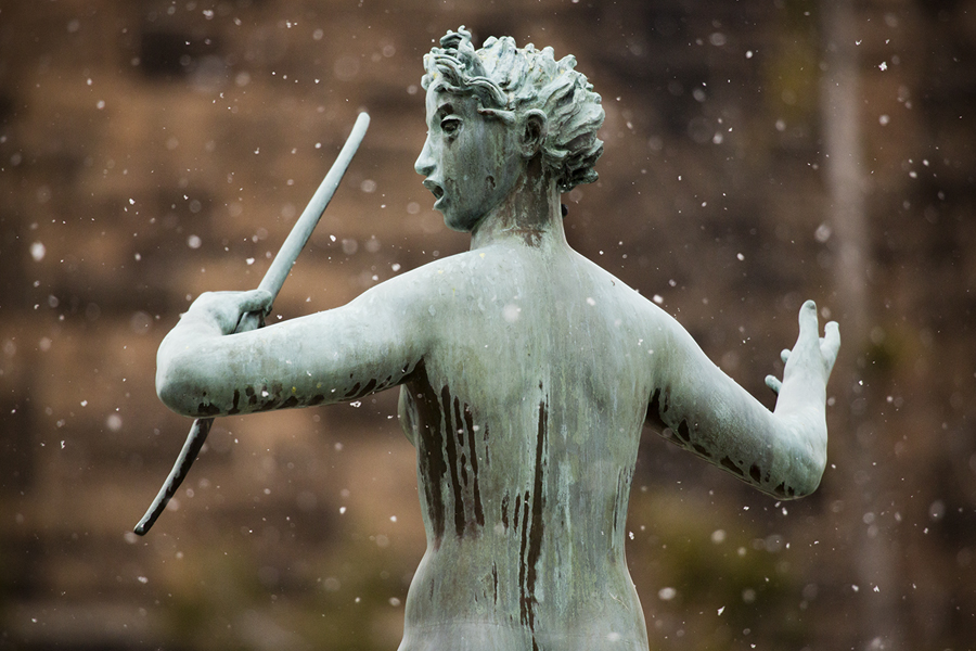 Snow falls around a female figure seen from behind