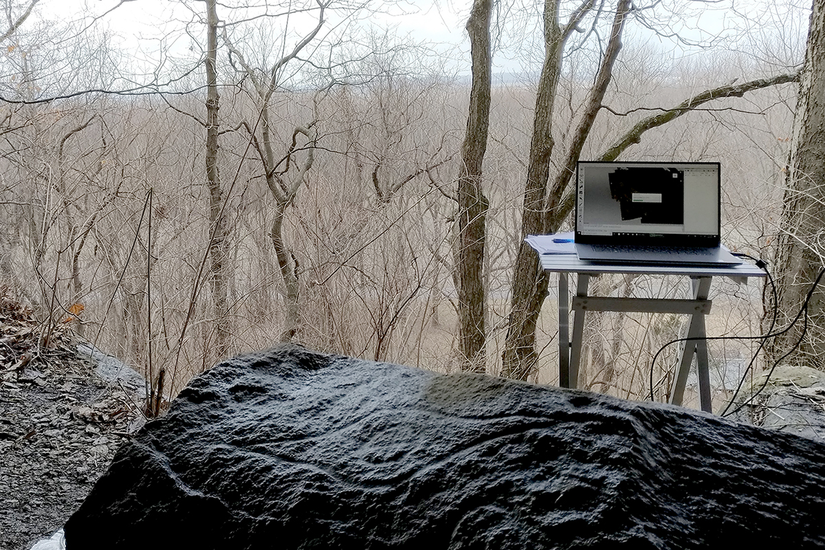 A limestone boulder with petroglyphs carved into it sits inside a rock shelter with a view toward the Mississippi River floodplain, below. One of the carvings is of a superhuman eye with a cross-in-circle motif at its center.