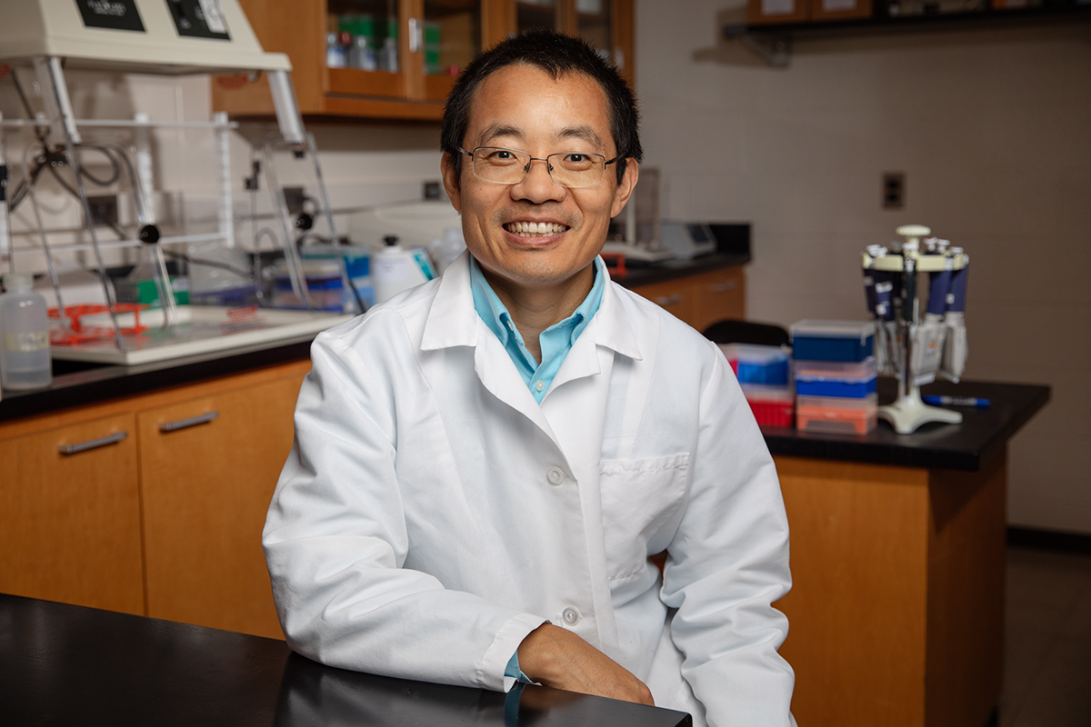 Dr. Leyi Wang in his lab, wearing his white veterinarian's coat.
