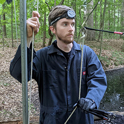 Photo of the author standing near a vertical pole used to secure the nets. He grasps a cord used to tighten the nets in place.